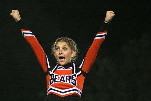 Young cheerleader screaming with hands in the air